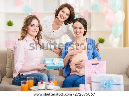 Beautiful pregnant woman with her friends and presents smiling at camera. - stock photo