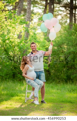 Beautiful pregnant woman with her husband in green garden - stock photo