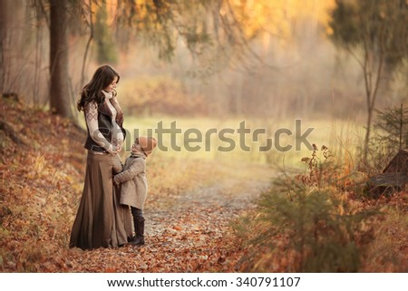 beautiful pregnant woman with her infant daughter little girl standing in the park or forest and looking at each other at autumn - stock photo