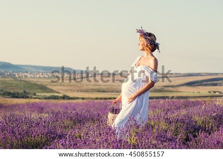 beautiful pregnant young woman in a white dress in lavender field - stock photo