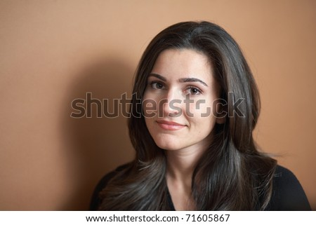 Beautiful pretty young woman on brown background - stock photo