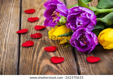 Beautiful purple and yellow tulips  with hearts on wooden background. - stock photo