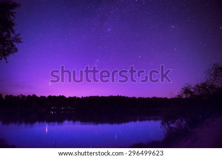 Beautiful purple night sky with many stars on a lake with forest on the other coast. Milkyway reflection in water - stock photo