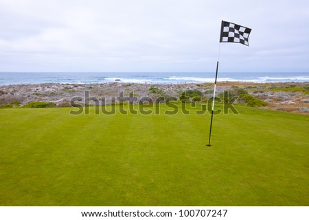Beautiful putting green and pin flag fluttering in the ocean breeze on a scenic, golf course situated on the Pacific Ocean. Dramatic cloudy sky overhead. - stock photo