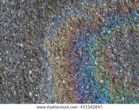 Beautiful rainbow color effect from oil on wet road, tarmac. After rain. - stock photo
