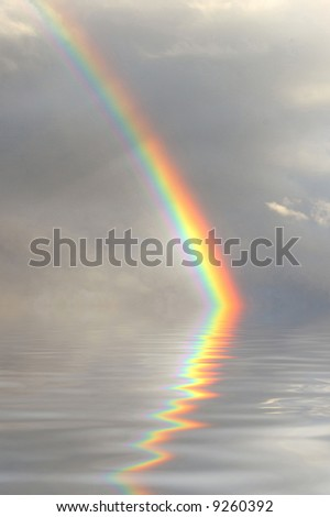 Beautiful rainbow reflected in the water - stock photo