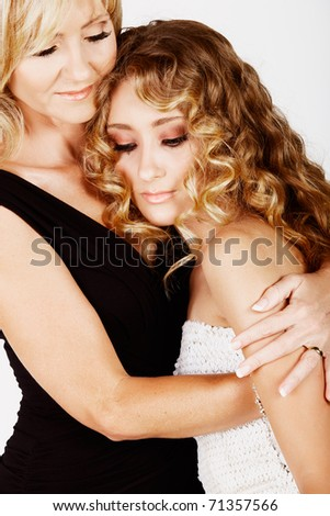 beautiful real couple mother in her 40s and teenage daughter wearing evening wear and make-up in studio, not isolated - stock photo