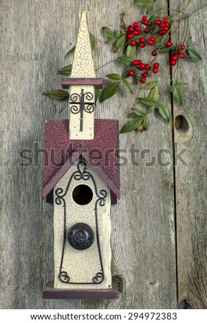 Beautiful red and white church birdhouse on rustic wooden fence with Nandina berries - stock photo
