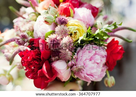 Beautiful red bouquet in bride's hands - stock photo