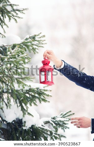 Beautiful red decorative Christmas lantern in hands outdoors - stock photo