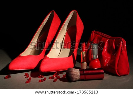 Beautiful red female shoes and cosmetics, on black background - stock photo