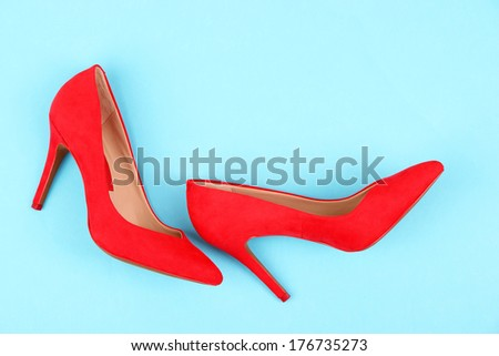 Beautiful red female shoes, on blue background - stock photo