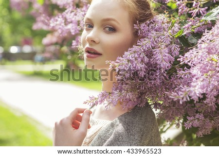 Beautiful red hair ginger slim young woman with fresh skin in casual outfit, posing with flowers. Sunny summer day in park (nature). Daylight - stock photo