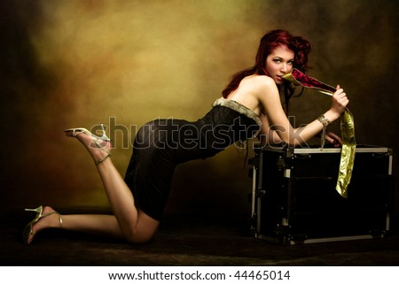 beautiful red hair woman leaned on trunk, studio shot - stock photo