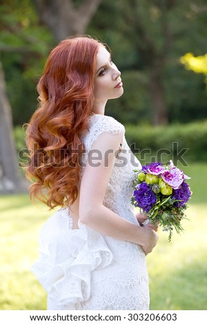 Beautiful red-haired bride in park. Wedding hairstyle - stock photo