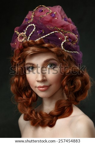 Beautiful red-haired girl in a headdress. Hair braided. Looking at the camera. - stock photo