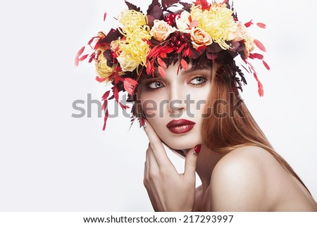 Beautiful red-haired girl with bright autumn wreath of leaves and flowers. Beauty face. Picture taken in the studio on a white background. - stock photo