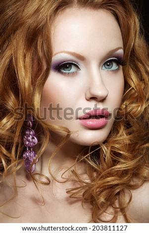 Beautiful red-haired girl with bright makeup and curls. Picture taken in the studio on a black background. - stock photo