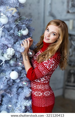 Beautiful red-haired girl with freckles and with blue eyes in a red sweater with white ornaments stands near a tree in the New year and smiling and holding a ball - stock photo