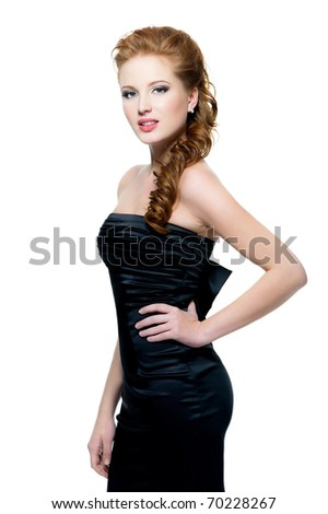 Beautiful  red-haired sensual woman in black dress posing on white background - stock photo