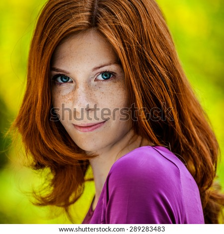 Beautiful red-haired smiling young woman in a purple blouse close up. - stock photo