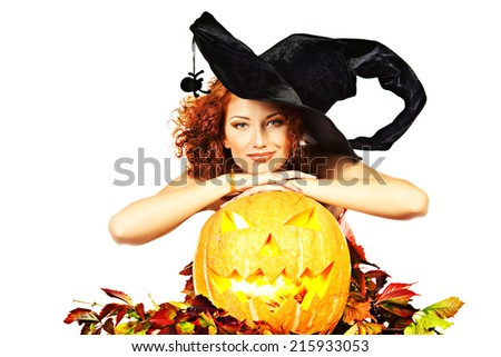 Beautiful red-haired witch casts a spell over pumpkins. Halloween. Isolated over white. - stock photo