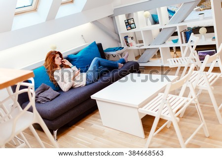 Beautiful red haired woman using phone while sitting on sofa - stock photo