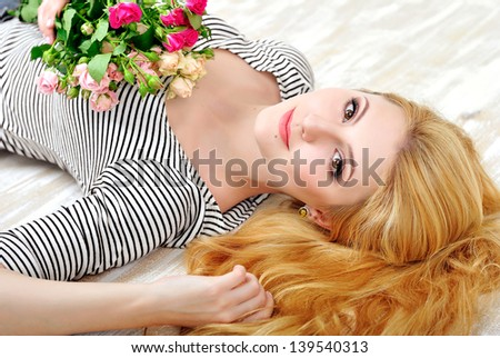 Beautiful red haired woman with bouquet of pink little roses lie on wooden floor - stock photo