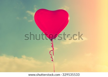 beautiful red hart shape balloon against sky with clouds, retro colors, sun flare - stock photo