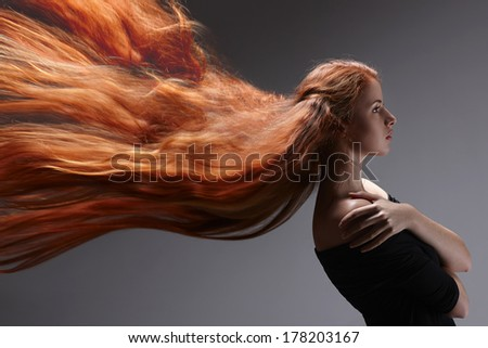 Beautiful red headed woman with long hair flying against gray background, side view - stock photo