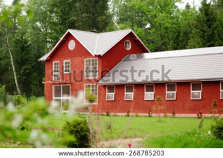 beautiful red horse barn among the green forest - stock photo