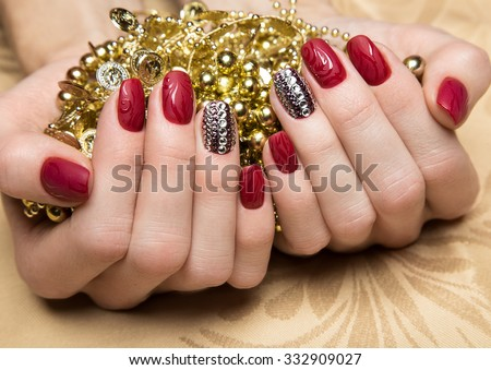 Beautiful red manicure with crystals on female hand. Close-up. Picture taken in the studio - stock photo