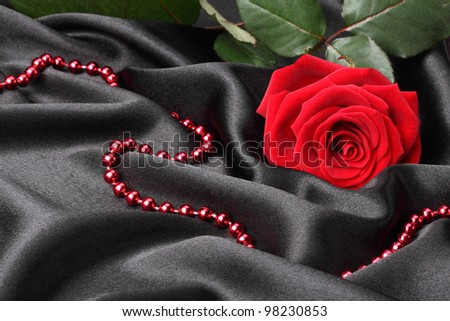 beautiful red rose on black background with necklace - stock photo