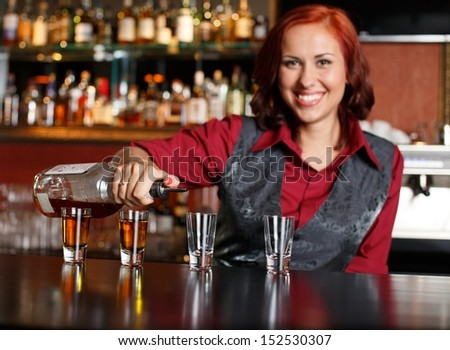 Beautiful redhead barmaid making shots - stock photo