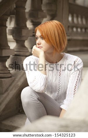 beautiful redhead dressed in white sweater posing on stairs - stock photo