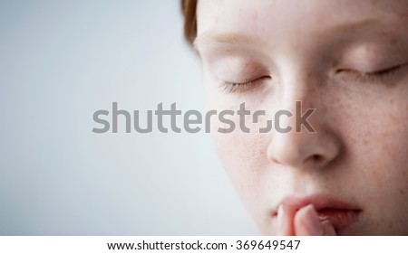 Beautiful redhead freckled young teen girl prays. Close up portrait of a female praying - stock photo