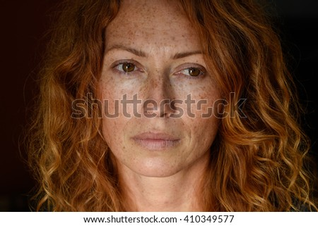 beautiful redhead freckled young woman with glance in eyes without make up black background close up - stock photo