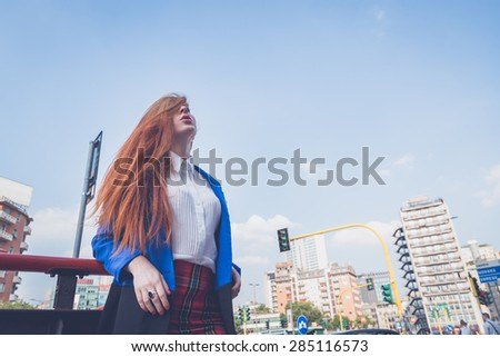 Beautiful redhead girl in blue jacket playing with her hair in an urban context - stock photo