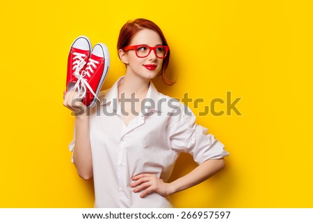 Beautiful redhead girl in white shirt with gumshoes on yellow background. - stock photo