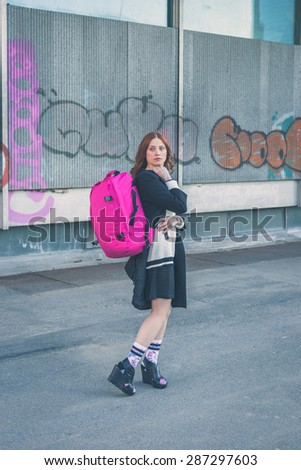 Beautiful redhead girl with long hair and blue eyes carrying a backpack in an urban context - stock photo