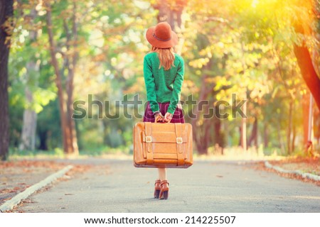 Beautiful redhead girl with suitcase in the park. - stock photo