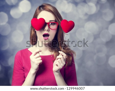 Beautiful redhead girl with two hearts. - stock photo