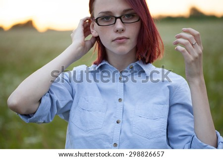 Beautiful redhead model in sunglasses outdoors - stock photo