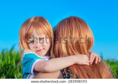 beautiful redhead mom with a young daughter gently hugging on the background of blue sky and green field - stock photo