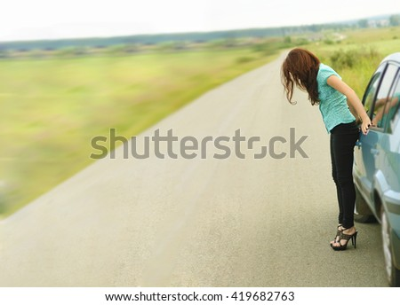 Beautiful redhead sexy woman, has black trousers and blue shirt , long hair, legs and elegant slim body, stand to road near car.  non urban . Real lady driver. Sunny day. no face. unrecognizable - stock photo