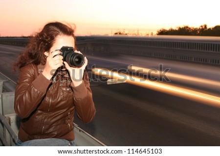 Beautiful redhead smiling girl-photographer with camera makes ni - stock photo