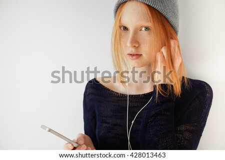 Beautiful redhead teenage girl in casual black top with no makeup standing isolated against white copy space wall for your information. Young woman listening to music on cell phone with headphones - stock photo