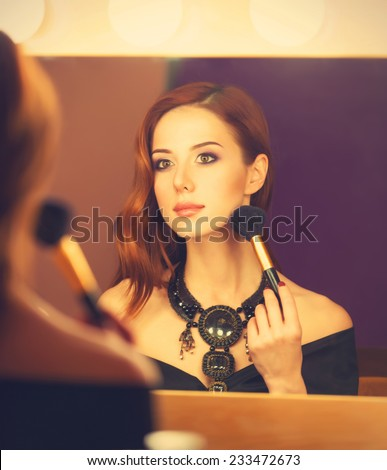 Beautiful redhead women applying makeup near mirror - stock photo