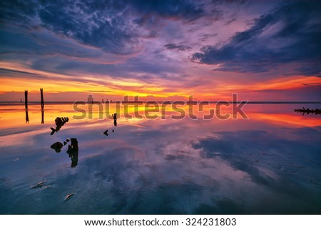 Beautiful reflections of sky and sunset on the beach. Nature composition - stock photo