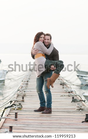 Beautiful relaxed couple on wooden pier in marina - stock photo